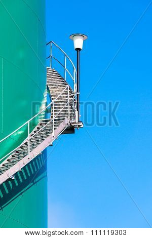 Green industrial storage tank against cloudless blue sky