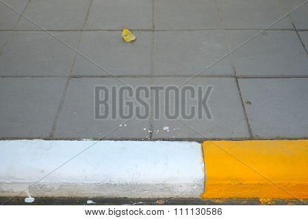 Yellow-white kerb line or curb stone border on the asphalt road.
