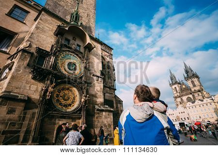 The unrecognizable man and boy are looking at astronomical clock