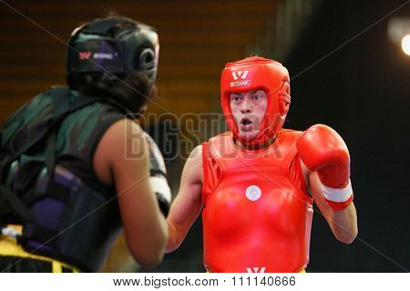 JAKARTA, INDONESIA - NOVEMBER 16, 2015: Ragan Beedy of the USA (red) fights Shanika Jayaweerage of Sri Lanka (black) in the women's 56kg Sanda event at the 13th World Wushu Championship 2015.