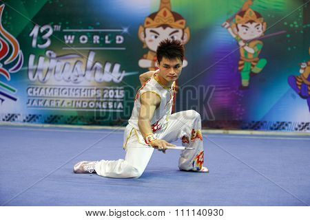 JAKARTA, INDONESIA - NOVEMBER 16, 2015: Jun Hua Huang of Macao performs the movements in the men's Nandao event at the 13th World Wushu Championship 2015 at the Istora Senayan Stadium.
