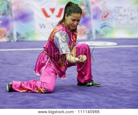 JAKARTA, INDONESIA - NOVEMBER 16, 2015: Elizabeth Lim of Australia performs her movements in the Women's Compulsory Nanquan event at the 13th World Wushu Championship 2015 in Istora Senayan Stadium.