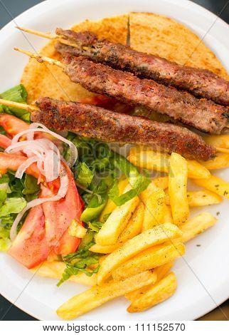 Souvlaki Or Kebab On Skewers With Potatoes And Vegetables.