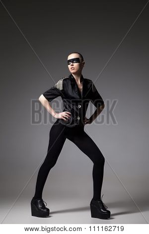 agressive bald woman in mask on gray background