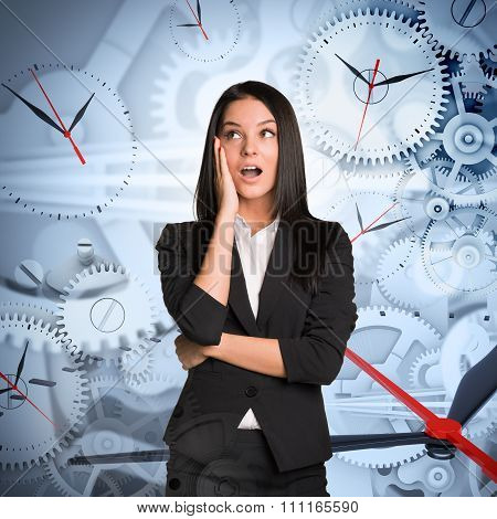 Surprised businesslady with clocks