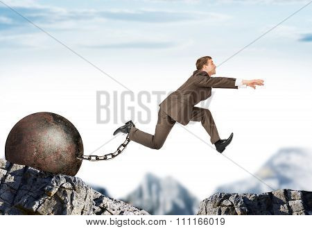 Young businessman jumping over gap