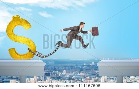 Man jumping over gap with gold dollar sign ballast