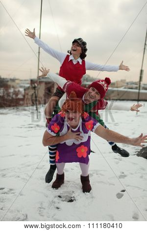 ST. PETERSBURG, RUSSIA - NOVEMBER 25, 2015: A. Yagudin (Karlsson), M. Petrova (Lillebror), and A. Tikhonov (Froken Bock) in characters of Karlsson-on-the-roof on the roof of the film studio Lenfilm