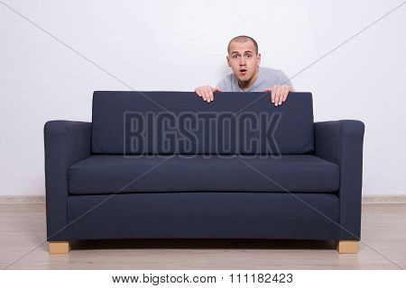 Young Man Hiding Behind A Sofa