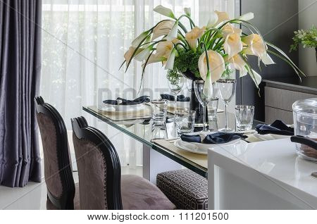 Table Set On Glass Dinning Table With Vase Of Flower