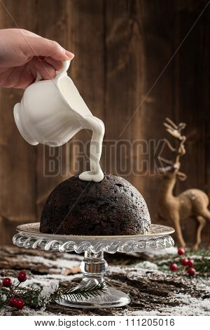 Pouring cream over Christmas pudding with festive setting