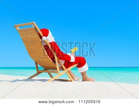 Christmas Santa Claus With Cocktail On Deckchair At Tropical Beach