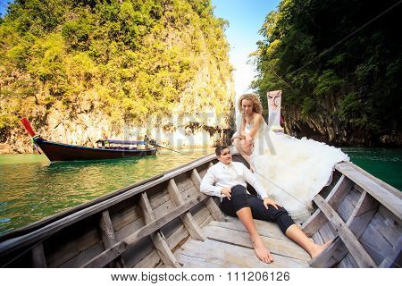 Groom Blonde Bride In Fluffy Sit On Nose Of Longtail Boat