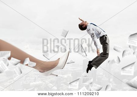 Big businesswoman foot kicking tiny businessman as dismissal concept