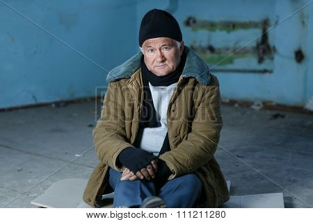 Homeless person sitting on the floor.