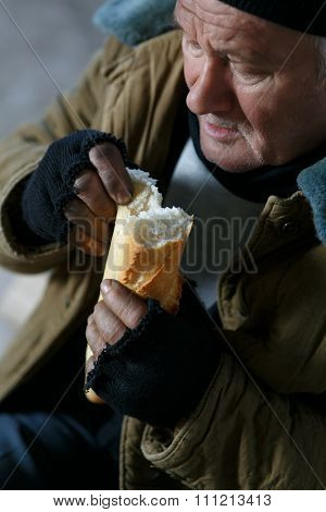 Depressed senior-aged beggar eating bread.
