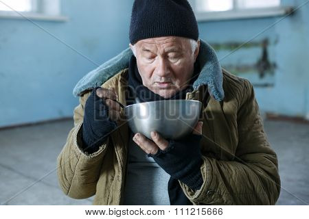 Homeless man is eating from his iron bowl.