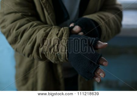Homeless man fixing his gloves.