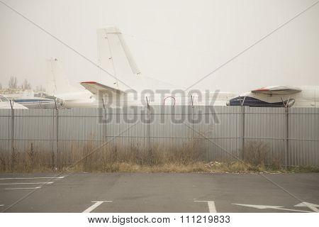 Airplanes behind metal fence