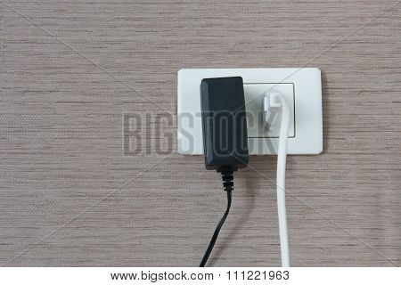 White And Black Cable Plugged In A White Electric Outlet Mounted On Wall.