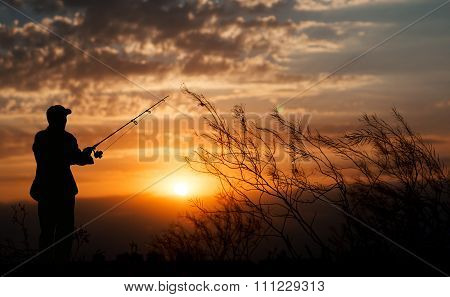 Fisherman Standing With Fishing Rod Near River On Background Of Plants And Beautiful Cloudy Sky With
