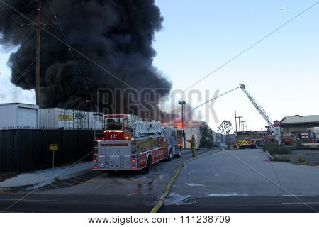HARBOR GATEWAY, CALIFORNIA- DECEMBER 12, 2015: Fire erupts at recycling yard in Harbor Gateway. Fire Fighters battle Hot Flames and Thick Black smoke trying to put out a fire, California Dec. 12, 2015