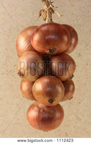 Braid Of Onions On A White Paper Background