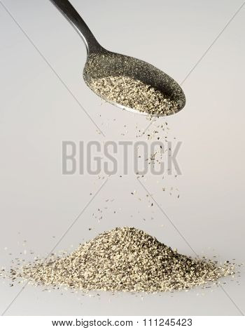 Black Pepper Falling From Tablespoon