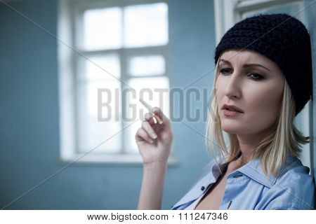 Depressed blond female drug addict with cigarette