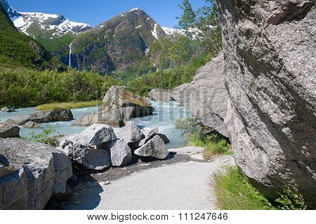 Norway. Water Flow From The Thawing Glacier Briksdayl In Mountains In The Summer Afternoon And A Tra