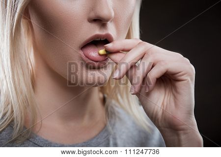Close up of face of young woman taking drug. The drug addict is standing and putting a pill into her mouth poster