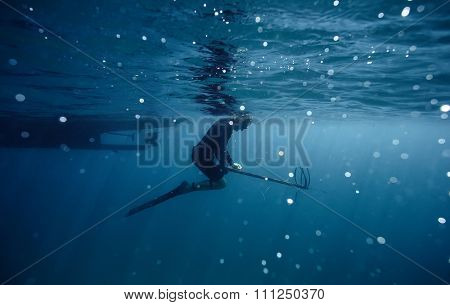 Spear-fisher at surface of water