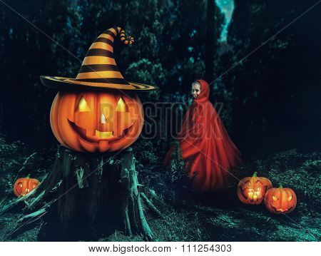 Little girl in a red gown in the forest with Helloween pumpkins