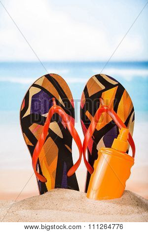 Slippers and sunblock in the sand