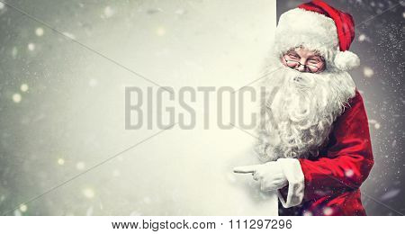 Happy Santa Claus pointing on blank advertisement banner background with copy space. Smiling Santa Claus pointing in white blank sign