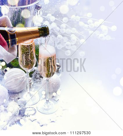 Christmas and New Year celebration with champagne. Holiday dinner table setting with Christmas decoration and sparkling wine. Champagne pouring.