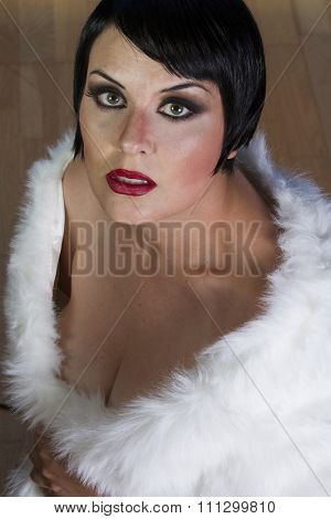 Old-fashioned beautiful brunette girl 20s style flapper with jewels and white fur