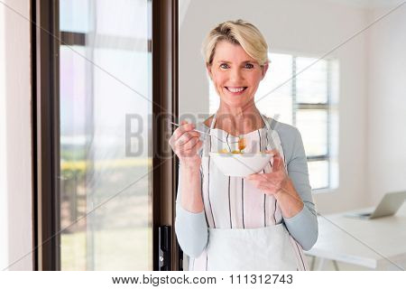 happy mid age woman eating fruit salad at home