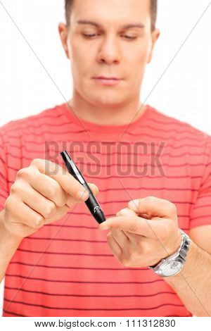 Vertical shot of a young man taking a blood sample with a glucometer to measure his blood sugar level isolated on white background