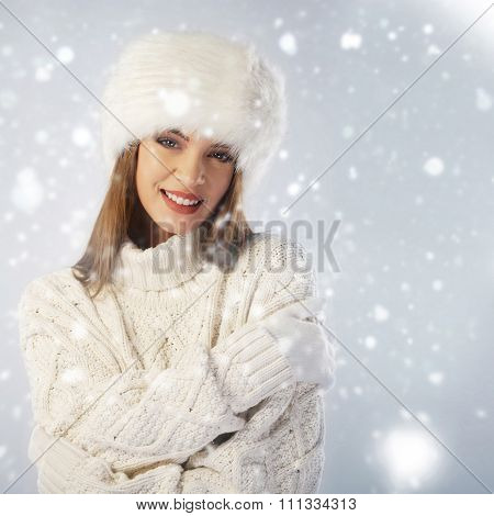 Winter Portrait. Woman Wearing Fur Cap And Knitted Sweater