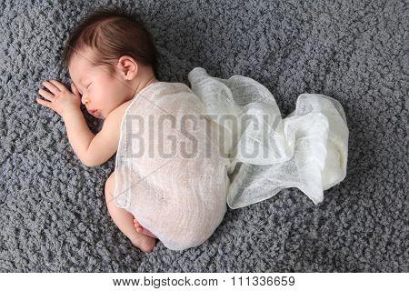 Newborn baby girl asleep on a blanket.