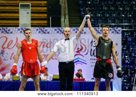 JAKARTA, INDONESIA - NOVEMBER 17, 2015: Andrei Nedikov of Belarus (red) loses to Gary Chandler of the USA (black) in the men's 65kg Sanda event at the 13th World Wushu Championship 2015.