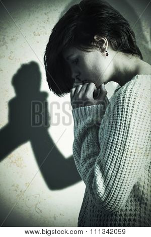 Sad pretty brunette holding her head against silhouette of man grabbing woman