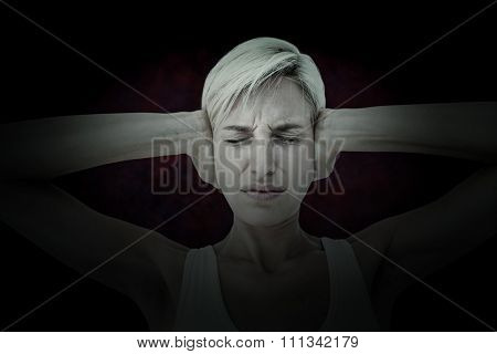 Upset woman covering her ears against dark background
