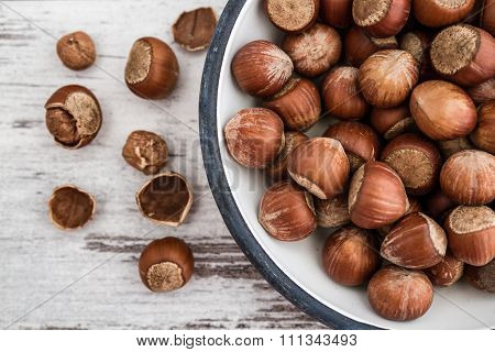 Hazelnuts In Enamel Bowl On White Wooden Table