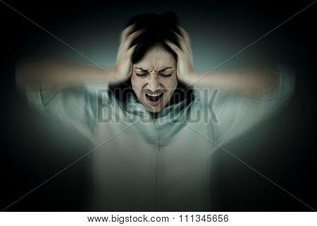 Depressed woman shouting against grey vignette