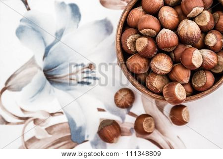 Top View Of Hazelnuts In Wooden Bowl On A Napkin With Flower Design