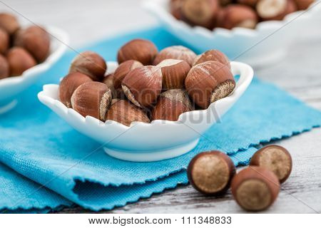Hazelnuts In White Bowls On A Blue Napkin