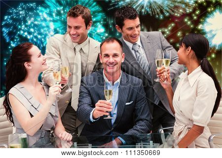 Smiling business team celebrating a success with champagne against colourful fireworks exploding on black background