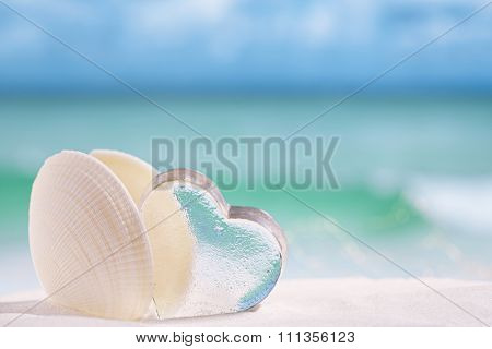 white sea shell  with heart glass on beach and sea blue background